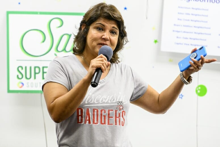 Photo: A woman addresses a room of visitors.