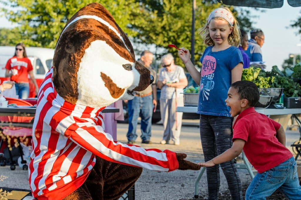 Photo: Young participant smiling while touching Bucky's paw