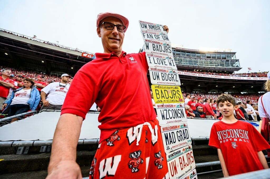Photo: A man displays a dozen Badger-themed license plates.