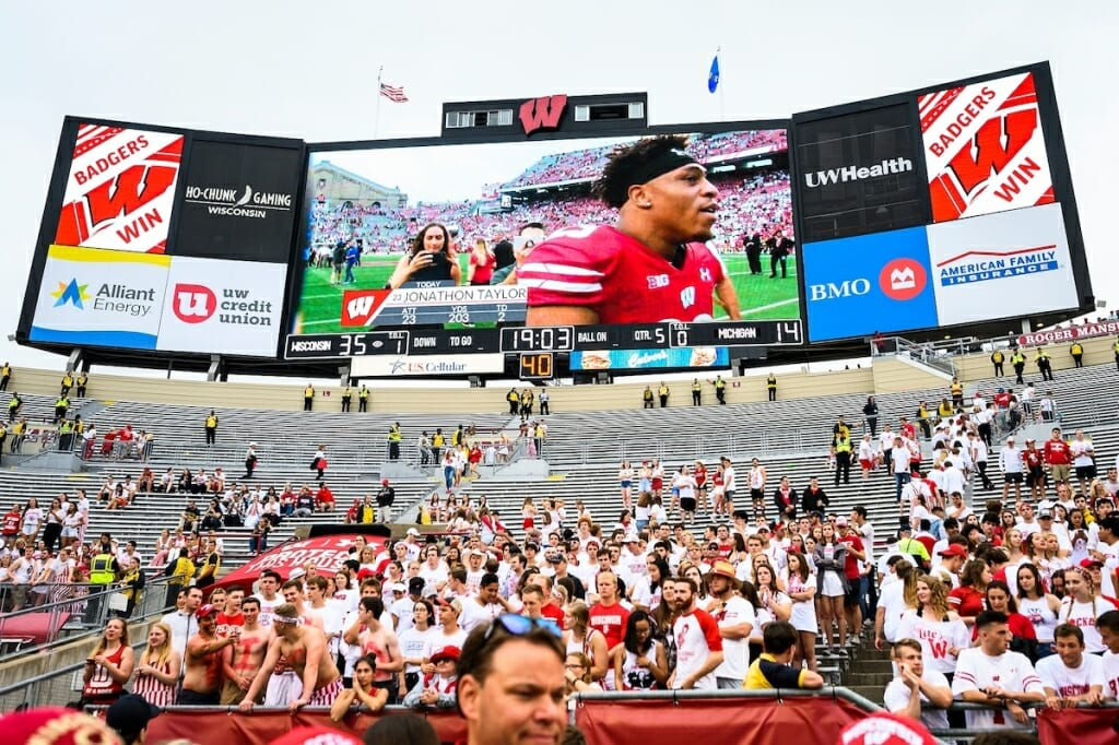 Fans cheer as the video scoreboard shows Wisconsin running back Jonathan Taylor (23) as he walks off the field. Taylor ran for 203 yards and two touchdowns during the game.