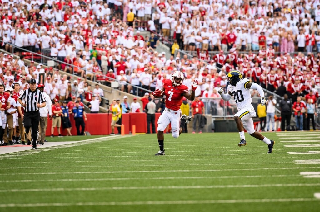 Photo: A Badger player runs, pursued by a Wolverine player, as fans cheer.