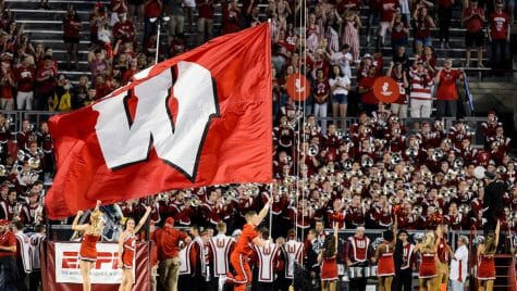 Photo of a cheerleader with the UW Spirit Squad running a large W flag across the field during a season-opening, night football game between the Wisconsin Badgers and the Western Kentucky Hilltoppers at Camp Randall Stadium at the University of Wisconsin-Madison on Aug. 31, 2018.
