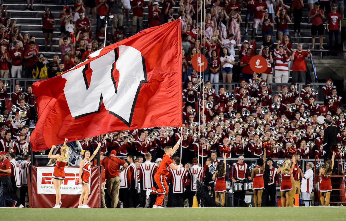 Photo of a cheerleader with the UW Spirit Squad running a large W flag across the field during a season-opening, night football game between the Wisconsin Badgers and the Western Kentucky Hilltoppers at Camp Randall Stadium at the University of Wisconsin–Madison on Aug. 31, 2018.