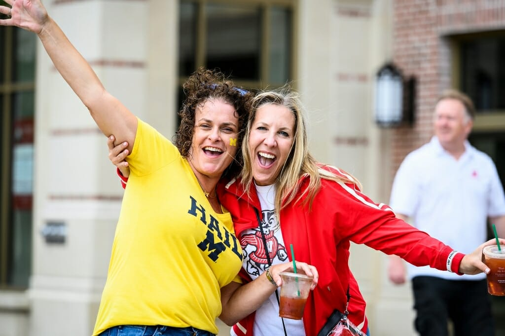 A woman wearing Michigan's maize and blue, and a woman wearing Wisconsin red