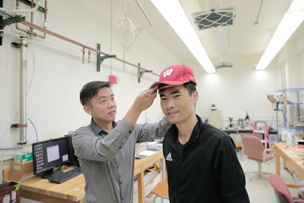 Photo: A man tries on a cap with a device in it, as another man helps.