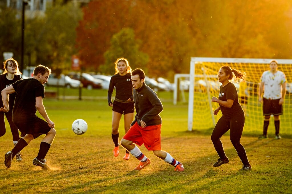 Photo: Soccer players run as the sun sets.