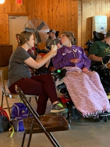 Photo: A caregiver helps feed a person in a wheelchair.