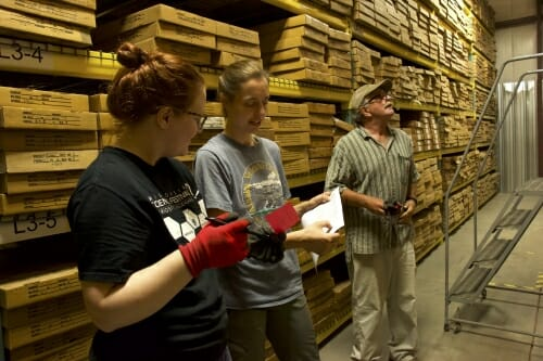 Photo: Three researchers in a warehouse.