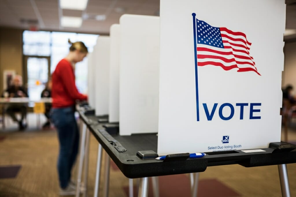 Photo: Closeup of American Flag VOTE sign on a polling booth