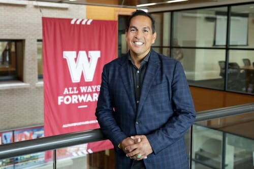 "Photo: Portrait of Aaron Bird Bear standing in front of a ""W All Ways Forward"" banner"