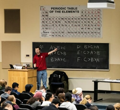 Photo: Bowman pointing at chalkboard below periodic table on wall