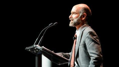 Photo: Jonathan Patz speaking into microphones at a podium