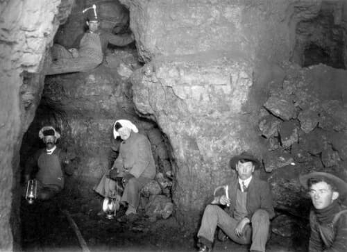 Black and white photo of a handful of miners sitting in a cave.