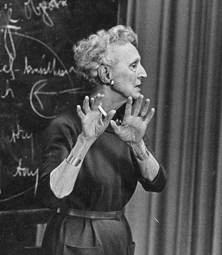 Photo: H'Doubler gesturing in front of a chalkboard