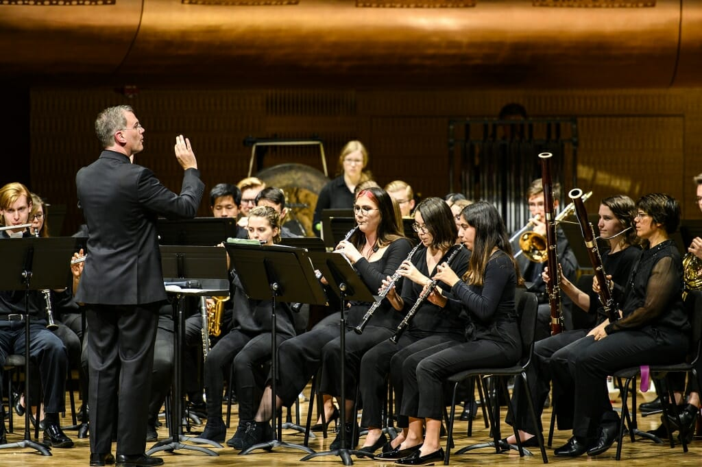 Photo: Conductor gesturing toward seated musicians playing wind instruments