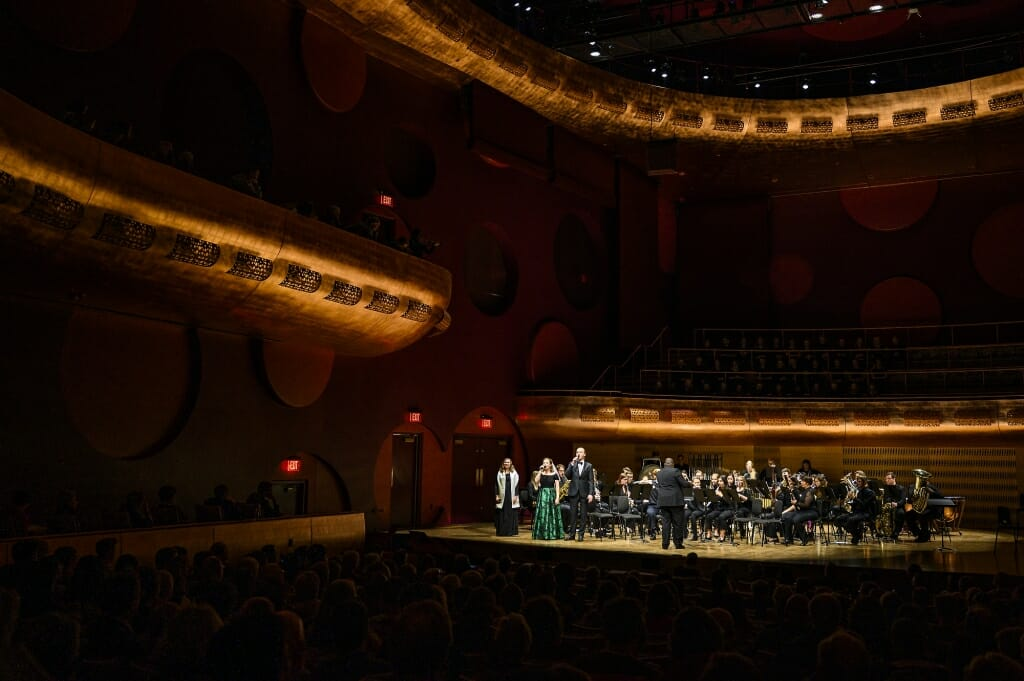 Photo: Singers standing on stage in front of seated musicians