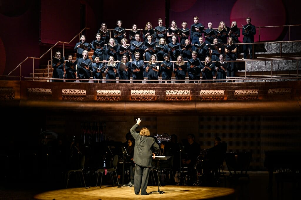 Photo: Conductor seen from behind with choir above on risers