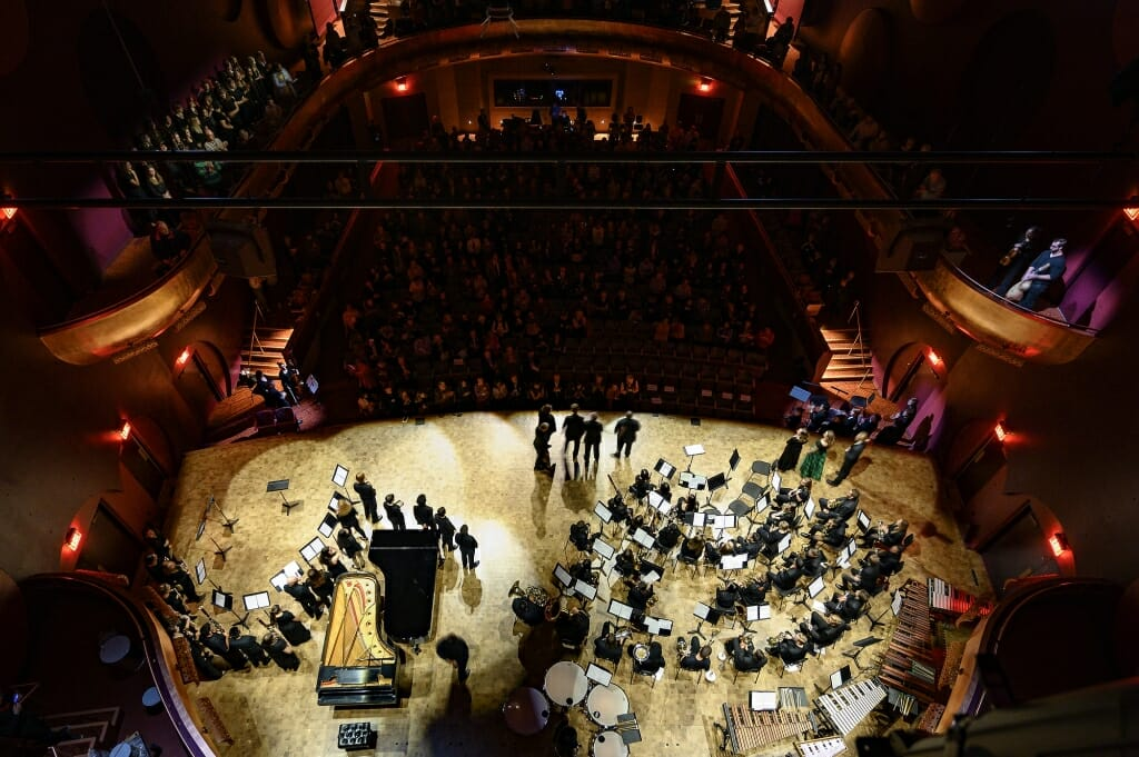 Photo: Overhead view of stage with musicians seated by music stands