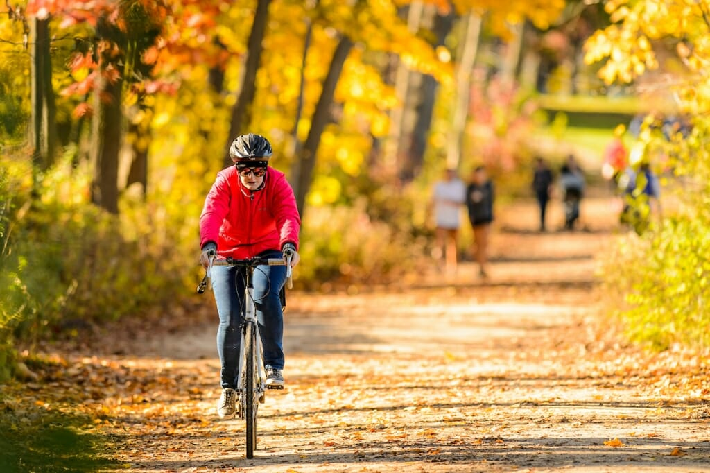 Photo: Bicyclist riding on path through trees with fall colors