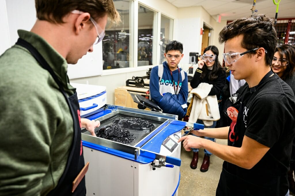 Makerspace staff Jake Rymsza, left, and Kirk Mendoza operate a thermoforming machine.