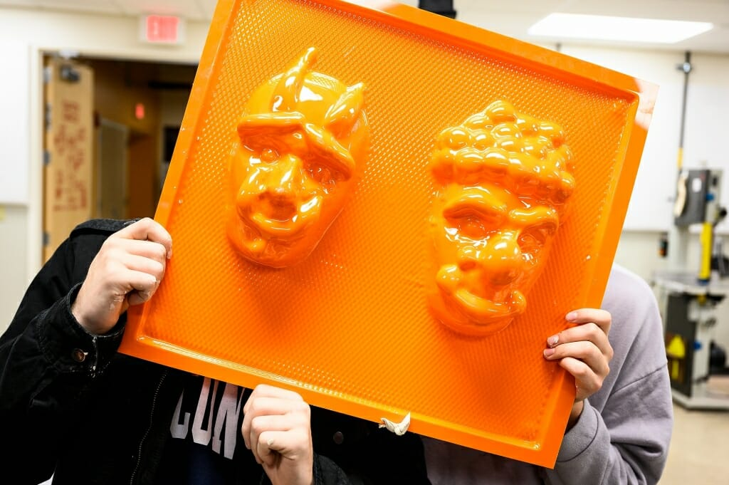 Photo: Person's hands holding up orange mold with 2 masks on it