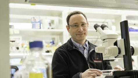 Photo: Newmark standing at microscope in lab