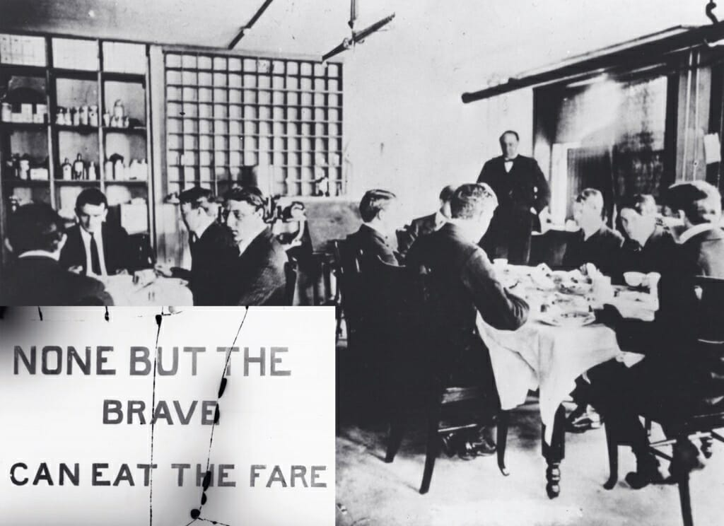 "Photo: Men sitting around dining tables behind a sign that says ""None but the brave can eat the fare"""