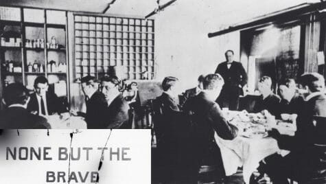 Photo: Men sitting around dining tables behind a sign that says