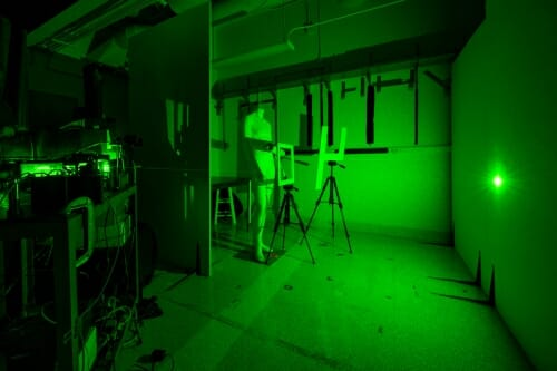 Photo: Darkened room with green laser light projected on wall