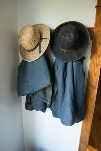 A pair of coats and hats hang on a wooden hook.