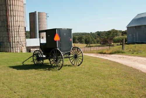 Photo: A wagon stands in a farm yard.
