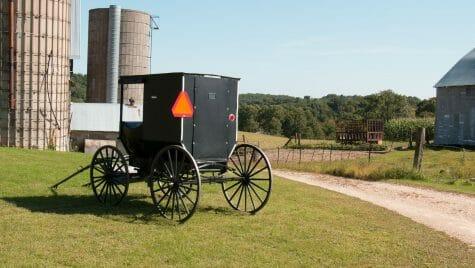 Photo: Amish wagon on farm next to silos