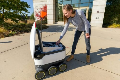 Photo: A woman takes her order out of a food delivery robot.