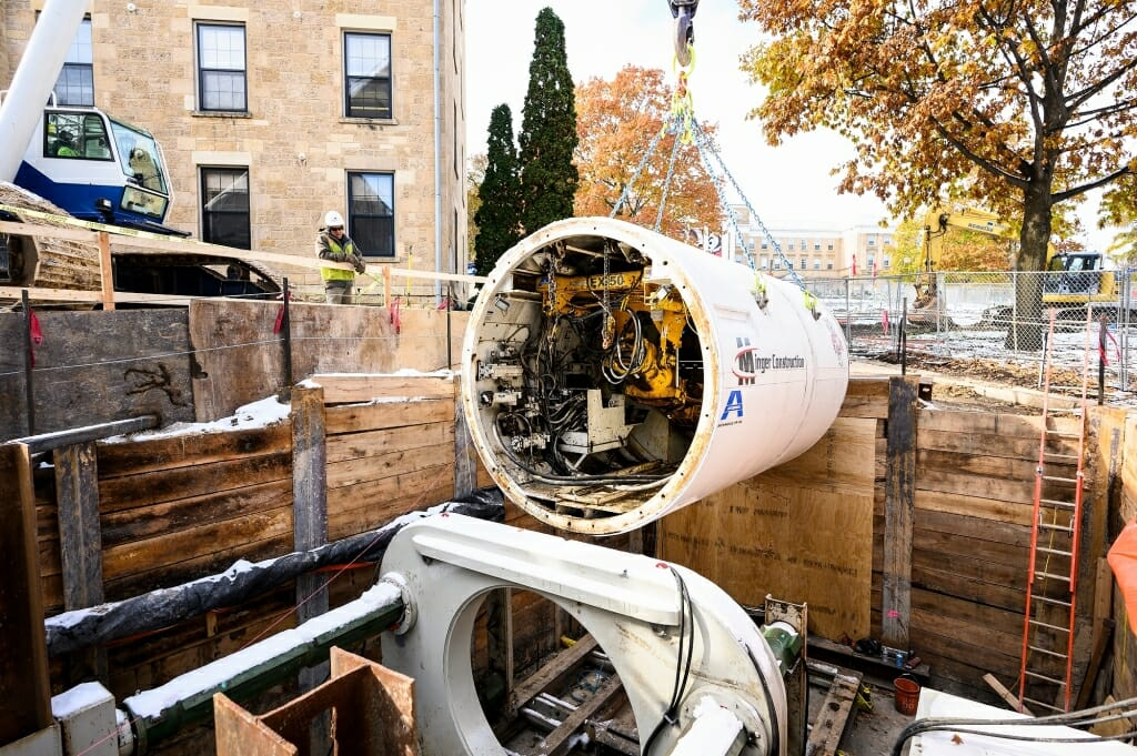The bore head is lowered down into the reinforced earthen pit between South Hall and the Law Building.