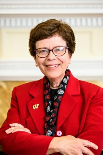 """UW-Madison Chancellor Rebecca Blank, wearing a red blazer with a """"Motion W"""" pin, is pictured in her office at Bascom Hall."""