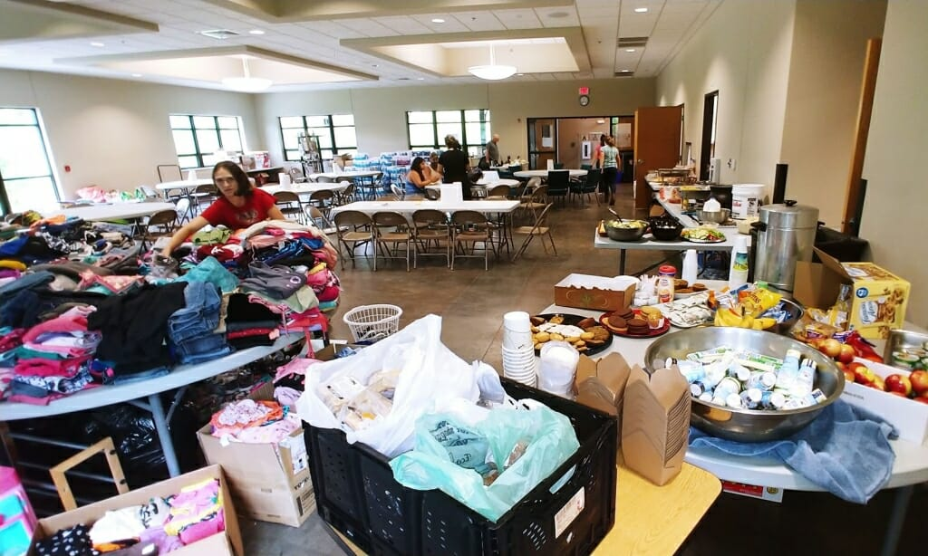 Photo: A big room is filled with supplies and people.