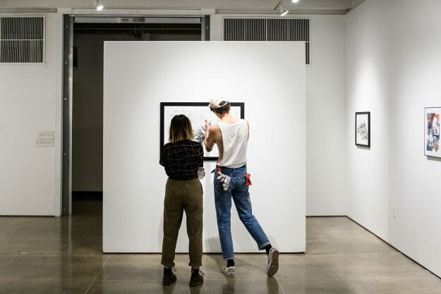 Photo: Two people closely examine an artwork.