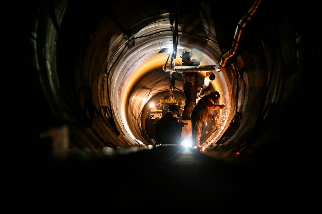 Photo: Workers weld and talk inside a darkened tunnel.