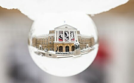 Bascom Hall and the Abraham Lincoln statue at the University of Wisconsin-Madison are seen in an inverted view looking through a polished crystal ball during a snowy winter day on Jan. 2, 2019. Hanging between the building column's are banners depicting a graphic of UW-Madison mascot Bucky Badger. (Photo by Jeff Miller / UW-Madison)