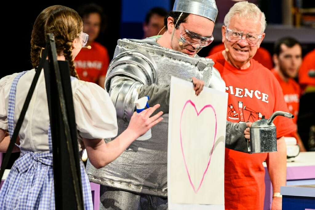 Photo of the Tin Man holding a piece of paper with a pink heart.