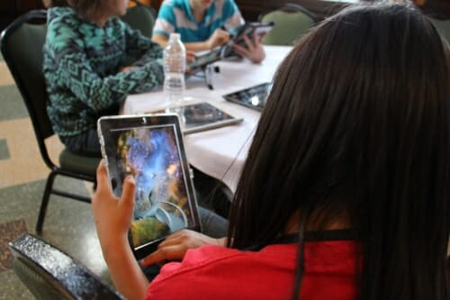 Photo: Child holding tablet computer with game shown on screen