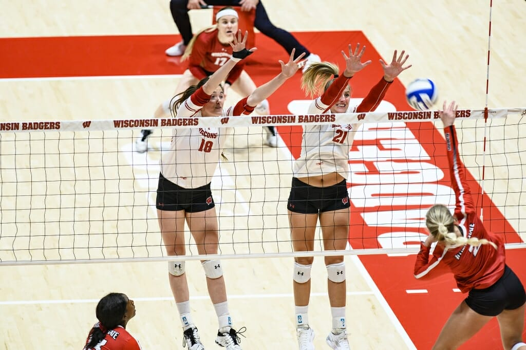 Photo: Danielle Hart (18) and Grace Loberg (21) go up for the block.