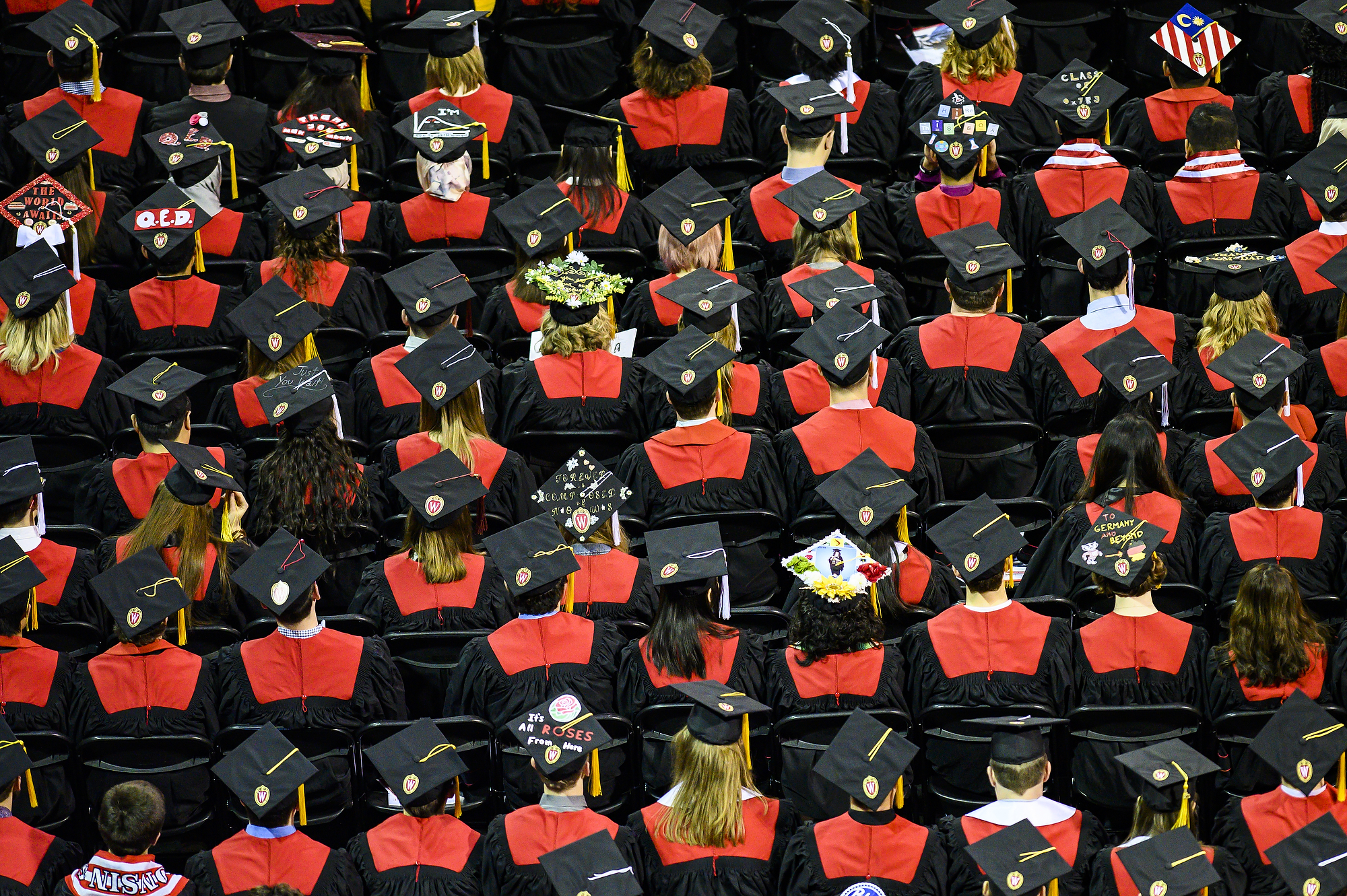 Photo from above of rows of seated graduates in caps and gowns.