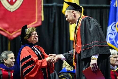 Photo of Chancellor Blank shaking a graduate's hand.