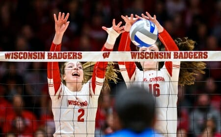 Photo: Wisconsin setter Sydney Hilley (2) and middle blocker Dana Rettke (16) block the ball at the net line.