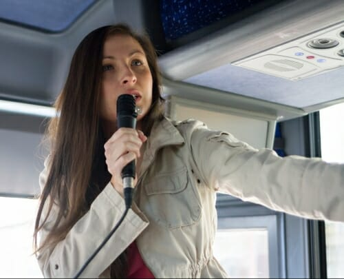 Photo: Melissa Metoxen standing inside a bus speaking into a microphone