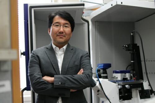 Photo: Portrait of Seungpyo Hong standing in his lab with arms folded