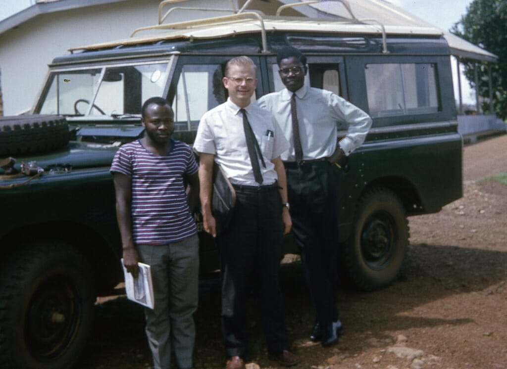Photo: M. Crawford Young, Isaac Ojok and James Katorobo posing in front of a large Jeep-like vehicle