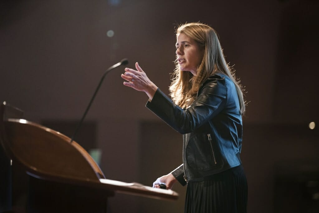 Photo: A woman speaks in a microphone.