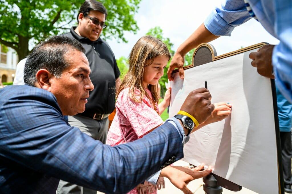 Photo: Bird Bear holding a crayon while Abangan-Brown Eagle rubs a crayon on paper covering plaque
